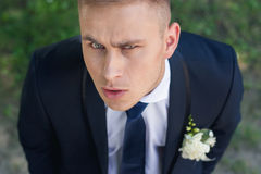 Frowning groom looks into the camera with your head Royalty Free Stock Images