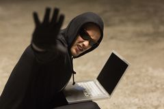 Frowning hacker in sunglasses gesturing Royalty Free Stock Photos