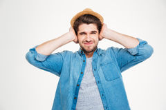 Frowning handsome young man covered ears by hands Stock Photography
