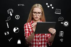 Surprised student frowning while looking at the screen of her tablet. Frowning. Interested young attentive student looking at the screen of her modern tablet and Stock Photos