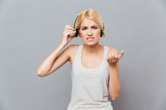 Frowning irritated young woman taking off headphones. Over gray background Royalty Free Stock Image