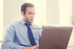 Frowning man biting his eyeglasses and using a laptop Royalty Free Stock Photos
