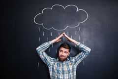 Frowning man covering from rain drawn on blackboard background Royalty Free Stock Photo