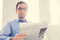 Frowning man looking at camera and holding a newspaper Royalty Free Stock Photos