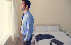 Frowning man standing looking out the window. In a bedroom at home Royalty Free Stock Photos