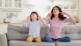 Frowning mom and son sit on couch with closed eyes and cover ears from noisy music or fight sounds
