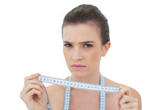 Frowning natural brown haired model holding a measuring tape Royalty Free Stock Image