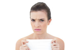 Frowning natural brown haired model holding a tissue Royalty Free Stock Images