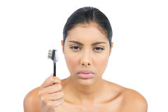 Frowning nude brunette holding eyebrow brush Royalty Free Stock Photography