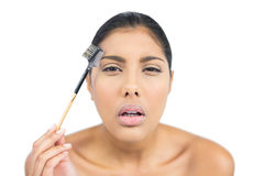 Frowning nude brunette using eyebrow brush Stock Photo