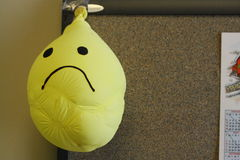 Frowning sad face smiley face yellow balloon deflated Stock Photography