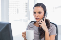 Frowning secretary answering phone. In her office Stock Photography