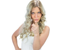 Frowning seductive model in white dress pointing at camera Royalty Free Stock Images