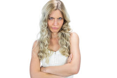 Frowning seductive model in white dress posing crossing arms Stock Image