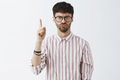 Frowning serious and strict male young teacher with beard in black trendy glasses and buttoned shirt raising index royalty free stock photography