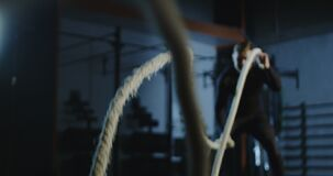Athlete working out with heavy ropes in gym. Frowning sportive man wriggling long heavy ropes working out and training endurance in dark gym. Slow motion 4K shot stock video footage