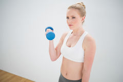 Frowning sporty blonde holding dumbbell Stock Photo