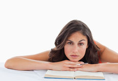 Frowning student head on her books. Against a white background Royalty Free Stock Images