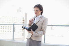 Frowning stylish brown haired businesswoman filling her schedule Royalty Free Stock Photography
