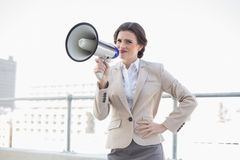 Frowning stylish brown haired businesswoman holding a megaphone Royalty Free Stock Images