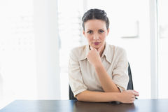Frowning stylish brunette businesswoman looking at camera and holding her head Royalty Free Stock Photo
