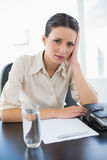 Frowning stylish brunette businesswoman sitting and holding her head Royalty Free Stock Photography