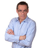 Frowning Surprised Man Looking over Glasses. Attractive Frowning Surprised Middle Age Man in Blue Shirt looking over Glasses Royalty Free Stock Photography