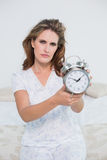 Frowning tired woman showing alarm clock. Frowning tired woman in bright bedroom showing alarm clock Stock Photography