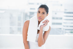 Frowning toned brunette holding towel Stock Photo
