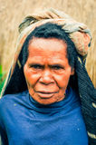Frowning woman with headcloth in Indonesia. Dani circuit, Indonesia - September 2015: Old native woman dressed in blue shirt with headcloth poses and frowns in Stock Photography