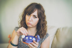 Frowning Woman Putting Coin in Airplane Bank Stock Photo