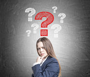 Frowning woman and red and white question marks Royalty Free Stock Photos