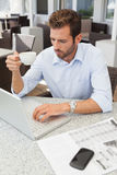Frowning young businessman using his laptop holding coffee cup Royalty Free Stock Image