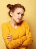 Frowning young woman thinking on yellow background Stock Photo