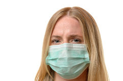Frowning young woman wearing a face mask Stock Image