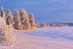 Frozen Äijäjärvi lake in Finnish Lapland in winter at sunset Royalty Free Stock Photo