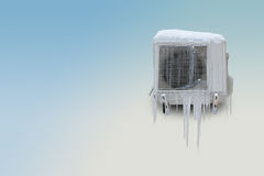 Frozen air conditioner with icicles on a blue white background. Copy space. Royalty Free Stock Photography