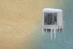 Frozen air conditioner with icicles. Heating and cooling concept. Vintage sand stone wall background. Toned photo. copy Royalty Free Stock Photo