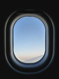Frozen airplane window view from inside, seeing blue and pink sky and part of aircraft`s wing. Stock Photography