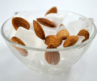 Frozen Almonds on Ice. Cold frozen almonds served on ice for dessert in transparent glass bowl Stock Images