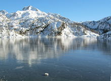 Frozen Alpine Lake. Frozen lake in a winter mountain landscape - Alps Stock Photo