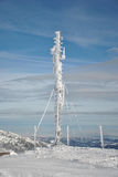 Frozen antenna. Telecommunication antenna on the top of the mountain, frozen and completely covered by snow and icicles against blue sky with some high clouds Stock Photography