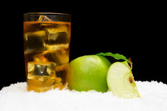 Frozen apple juice,ice cubes and apple with leaves on black on snow Royalty Free Stock Photography
