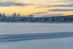 Frozen arctic lake &  forests under an orange sunset sky