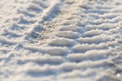 Tire tracks in the frozen snow - ice - detail. Frozen auto tyre tracks in the snow stock photography