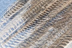 Tire tracks in the frozen snow - ice - detail. Frozen auto tyre tracks in the snow royalty free stock image