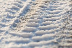Tire tracks in the frozen snow - ice - detail. Frozen auto tyre tracks in the snow stock image