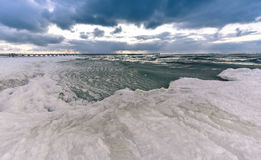 Frozen Baltic seacoast. Wide angle landscape view of frozen Baltic seacoast and bridge, Palanga Lithuania, wintertime Royalty Free Stock Photos