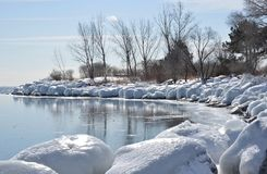 Frozen bay and ice rimmed shore HBPE. Reflections of bare trees fall onto newly frozen smooth surface of Lake Ontario along ice encrusted shoreline royalty free stock images