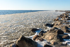 Frozen beach near shipyard and sea port Royalty Free Stock Images